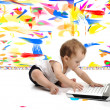 Stock Photo: Little baby boy is sitting on floor with his laptop, isolated over white wall, in messy painted room with many colors around