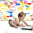 Little baby boy is sitting on floor with his laptop, isolated over white wall, in messy painted room with many colors around — Stock Photo