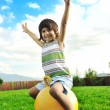 Little happy boy playing with big ball and jumping with wide opened arms in air — Stock Photo