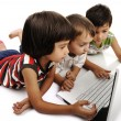 Group of children playing on white laptop together. Isolated on white. — Foto de Stock