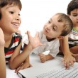 Stock Photo: Group of children playing on white laptop together. Isolated on white.