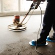 Stock Photo: Equating and leveling fresh cement for the floor, by one worker