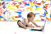 Little baby boy is sitting on floor with his laptop, isolated over white wall, in messy painted room with many colors around — Zdjęcie stockowe