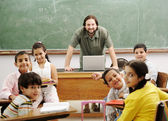 Teacher with children in classroom — Stock Photo