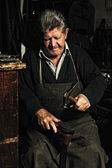Old man, shoemaker, repairing old handmade shoe in his workshop — Stock Photo