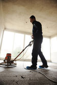 Equating and leveling fresh cement for the floor, by one worker — Stock Photo