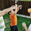 Stock Photo: Happy children playing with bubbles outdoor, selective focus - kids in motion