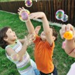 Happy children playing with bubbles outdoor, selective focus - kids in motion — Stock Photo
