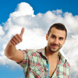Happy casual young man showing thumb up and smiling isolated on — Stock Photo