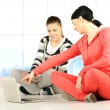 Two girls doing yoga and fitness using laptop in bautiful bright surround - Stock Photo
