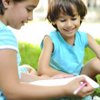 Two kids writing together outdoor — Stock Photo