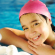 Little kid girl is swimming on pool - Foto Stock