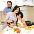 Happy family of four members in kitchen — Stock Photo