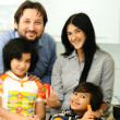 Happy family of four members in kitchen - Stockfoto