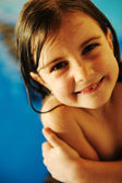 Little cute girl in pool smiling, grainy photo — Стоковое фото