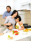 Happy family of four members in kitchen — Stok fotoğraf