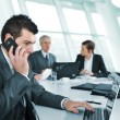 Foto Stock: Business man speaking on the phone while in a meeting