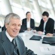 Senior businessman at a meeting. Group of colleagues in the back — Stock Photo #21529925