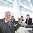 Senior businessman laughing at office meeting — Stock fotografie #21529971