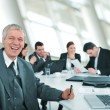 Stock Photo: Senior businessman at a meeting. Group of colleagues in the back