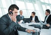 商务男人手机虽然在一次会议上发言 — 图库照片
