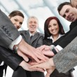 Group of happy smiling executives placing their hands together — Stock Photo #21530223