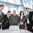 Multi aged business standing around the table at office - Stock Photo