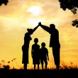 Стоковое фото: Silhouette, group of happy children playing on meadow, sunset, s