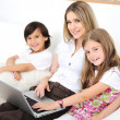 Mother with daugther and son using laptop on sofa indoor — Stock Photo #21532613