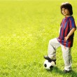 Happy kid playing football in a park outdoors — Stock fotografie