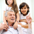 Grandfather with children, senior man at home with family — Stockfoto