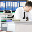 Tired businessman working in office — Stock Photo