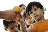 Hungry children in refugee camp, distribution of humanitarian food — Fotografia Stock