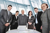 Multi aged business standing around the table at office — Stock Photo