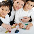 Mother working with sons on homework project — Stock Photo