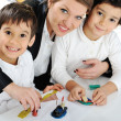 Mother working with sons on homework project — Stock Photo #21542183