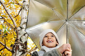 Happy kid and autumn leaves in a park — Stock Photo