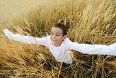 Happy child at harvest field — Stock Photo