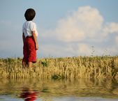 Kid standing on meadow alone — Stock Photo