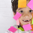 Stock Photo: Little boy with memo notes on his face