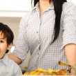 Stock Photo: Little boy in kitchen with mother