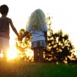 Happy children in nature at sunset — Stock Photo