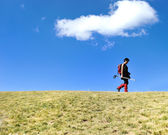 Woman mountaneering on grassland with cloud as copy space — Stock Photo
