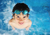 Kid with swimming glasses in water pool — Stock Photo