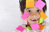Little boy with memo notes on his face — Stock Photo