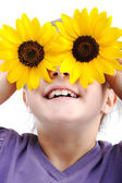 Happy little girl with sunflowers on eyes — Stock Photo