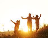 çayır üzerinde günbatımında çalışan çocuklar — Stok fotoğraf