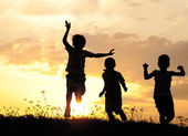 Children running on meadow at sunset — Stok fotoğraf