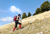 Walking uphill woman trekking and hiking mountaineering — Stock Photo