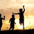 Children running on meadow at sunset — Stockfoto
